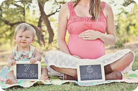 As placas mostram a idade dos dois irmãos (dentro e fora da barriga!)