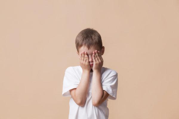 menino de pé com as mãos no rosto