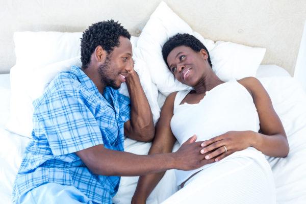 casal com mulher grávida conversando deitados na cama