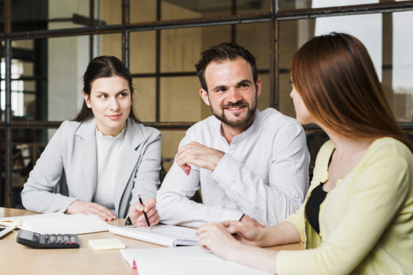 mulher conversando com casal de chefes no escritório