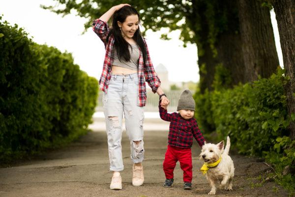 Mãe e criança caminhando com cachorro
