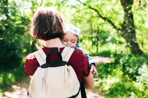 Superproteção - Mãe levando criança no colo na natureza