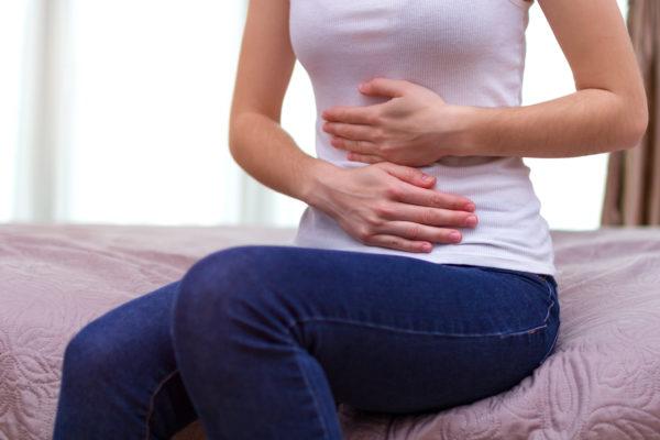 mulher sentada com dor abdominal