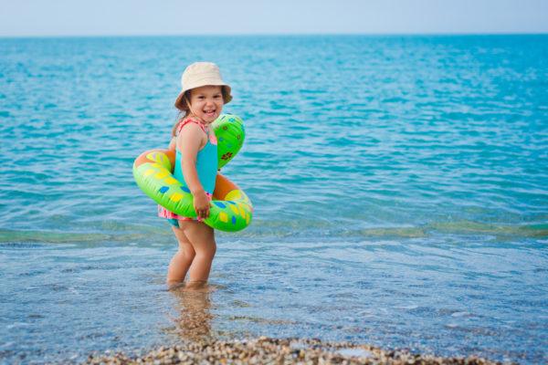 Criança com boia no mar