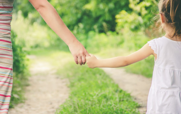 Criança e mãe andando de mãos dadas na natureza
